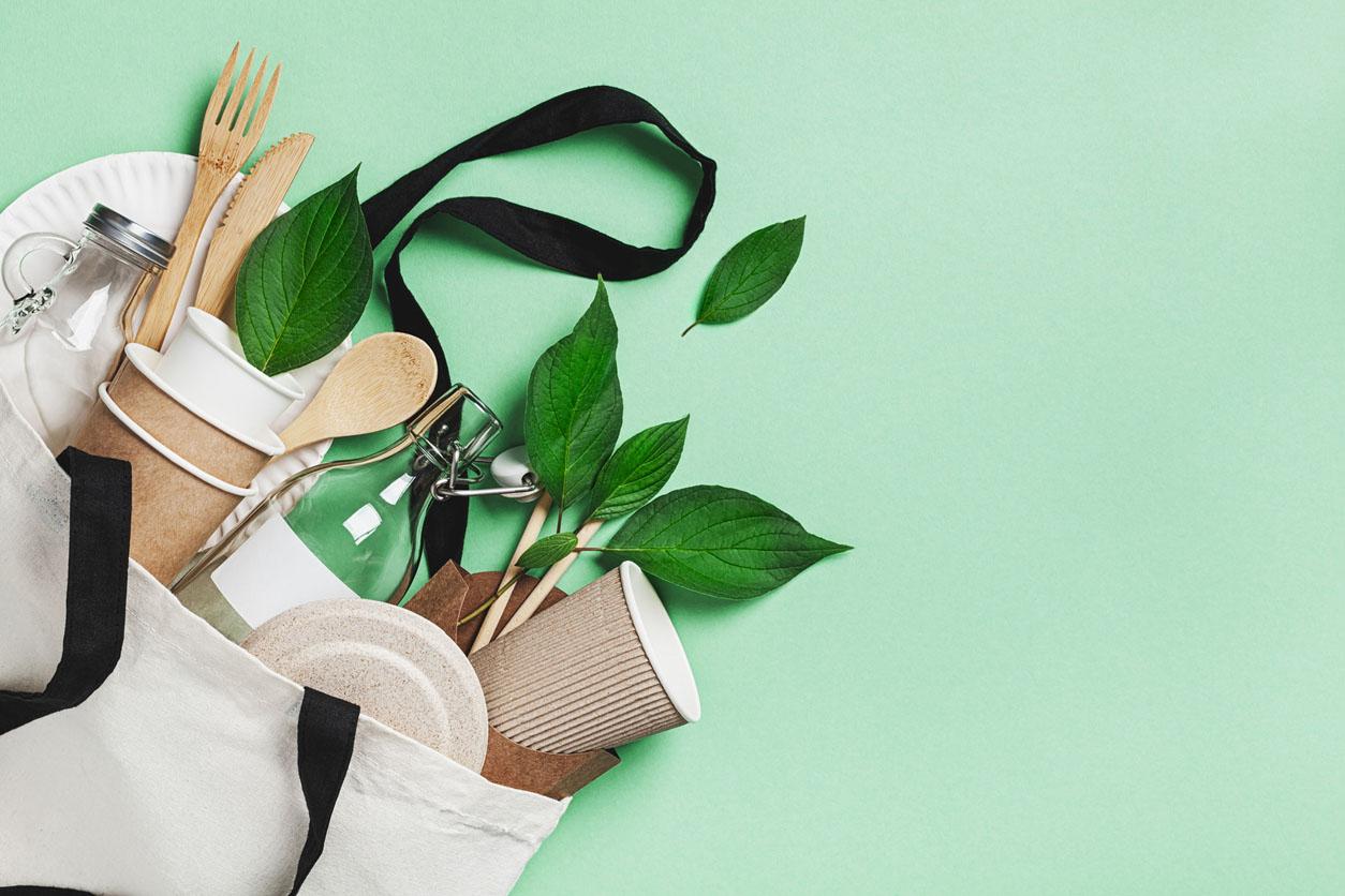 Ensemble sans plastique avec sac en coton écologique, pot en verre, feuilles vertes et vue du haut de la vaisselle recyclée. Zéro déchet, concept écologique
