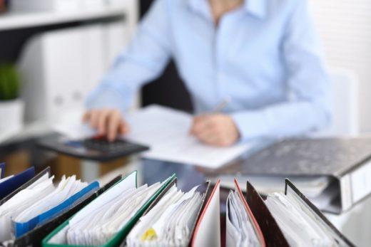 Reliures avec papiers attendent d'être traitées avec la femme d'affaires ou secrétaire en flou