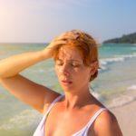 Woman Having Sun Stroke On Sunny Beach. Woman On Hot Beach With Sunstroke.