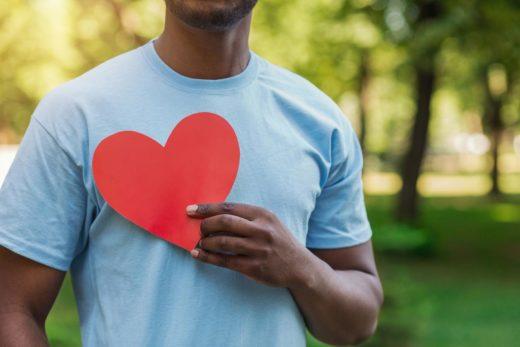 Homme retenant le coeur rouge sur sa poitrine