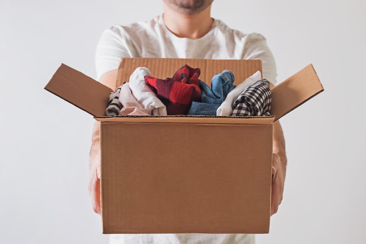 Homme tenant une boîte en carton pleine de vêtements plan rapproché