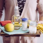Femme tenant les ingrédients écologiques de nettoyage à la maison, vinaigre blanc, citron, bicarbonate de soude, acide citrique