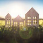 Maison écologique de modèle de bois dans le champ vide au coucher du soleil
