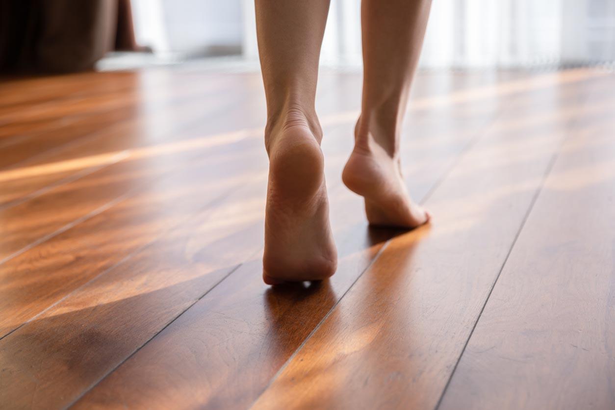 Femme marchant pieds nus sur des orteils à la vue chaude de plan rapproché de plancher