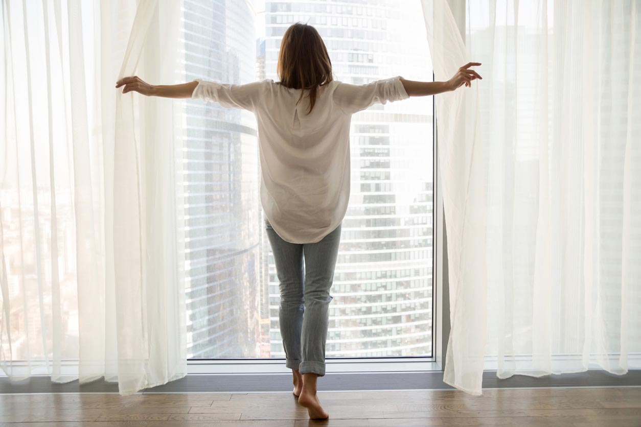 Woman Standing Looking Out Of Window Opening Curtains, Rear View