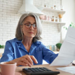 Senior Mature Business Woman Holding Paper Bill Using Calculator, Old Lady Managing Account Finance, Calculating Money Budget Tax, Planning Banking Loan Debt Pension Payment Sit At Home Kitchen Table.